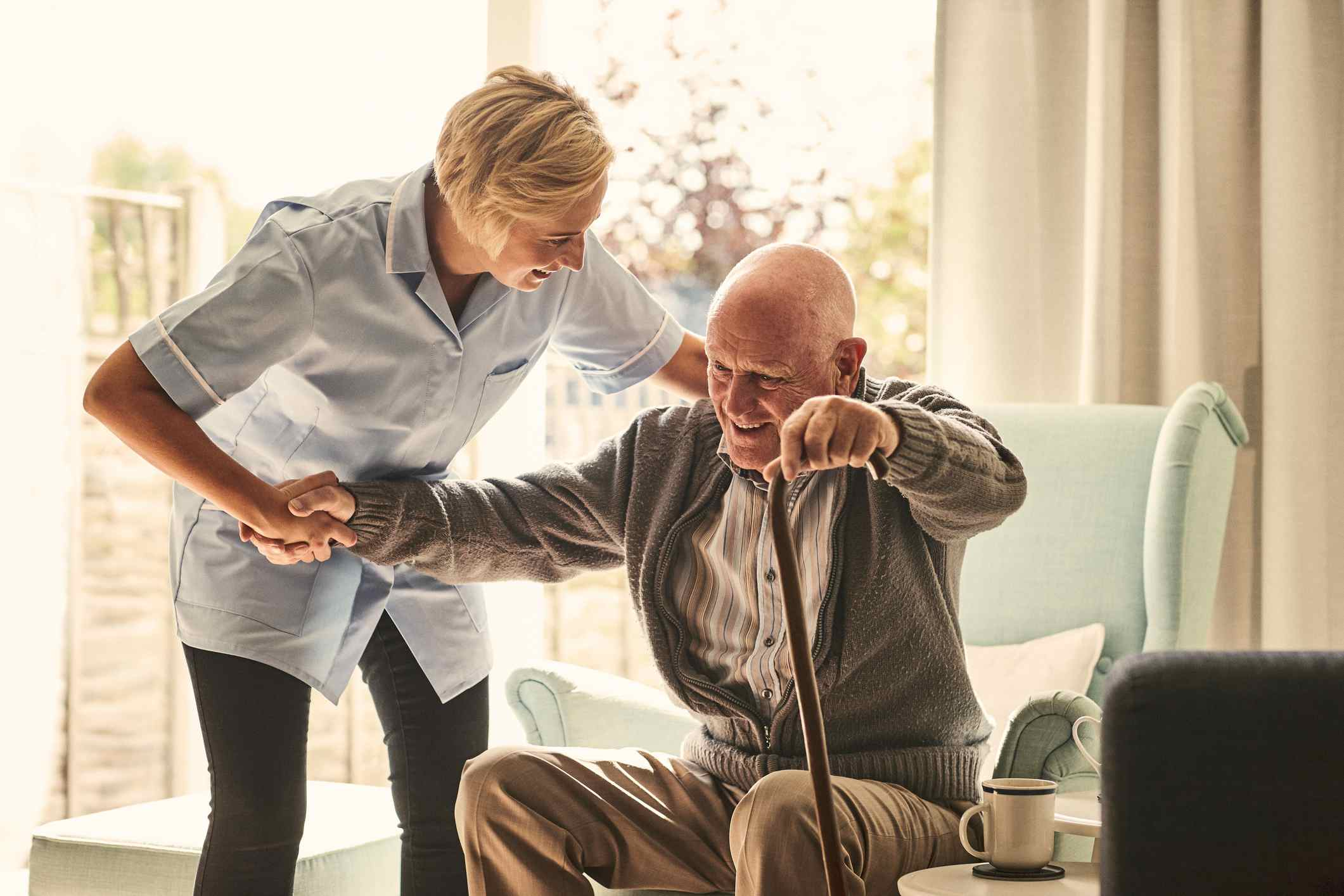 Female healthcare worker supporting senior man at care home