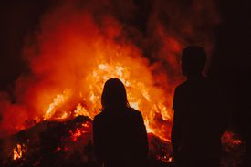 Silhouette Man And Woman Sitting By Bonfire At Night