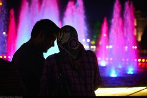 a couple standing in front of a fountain at night