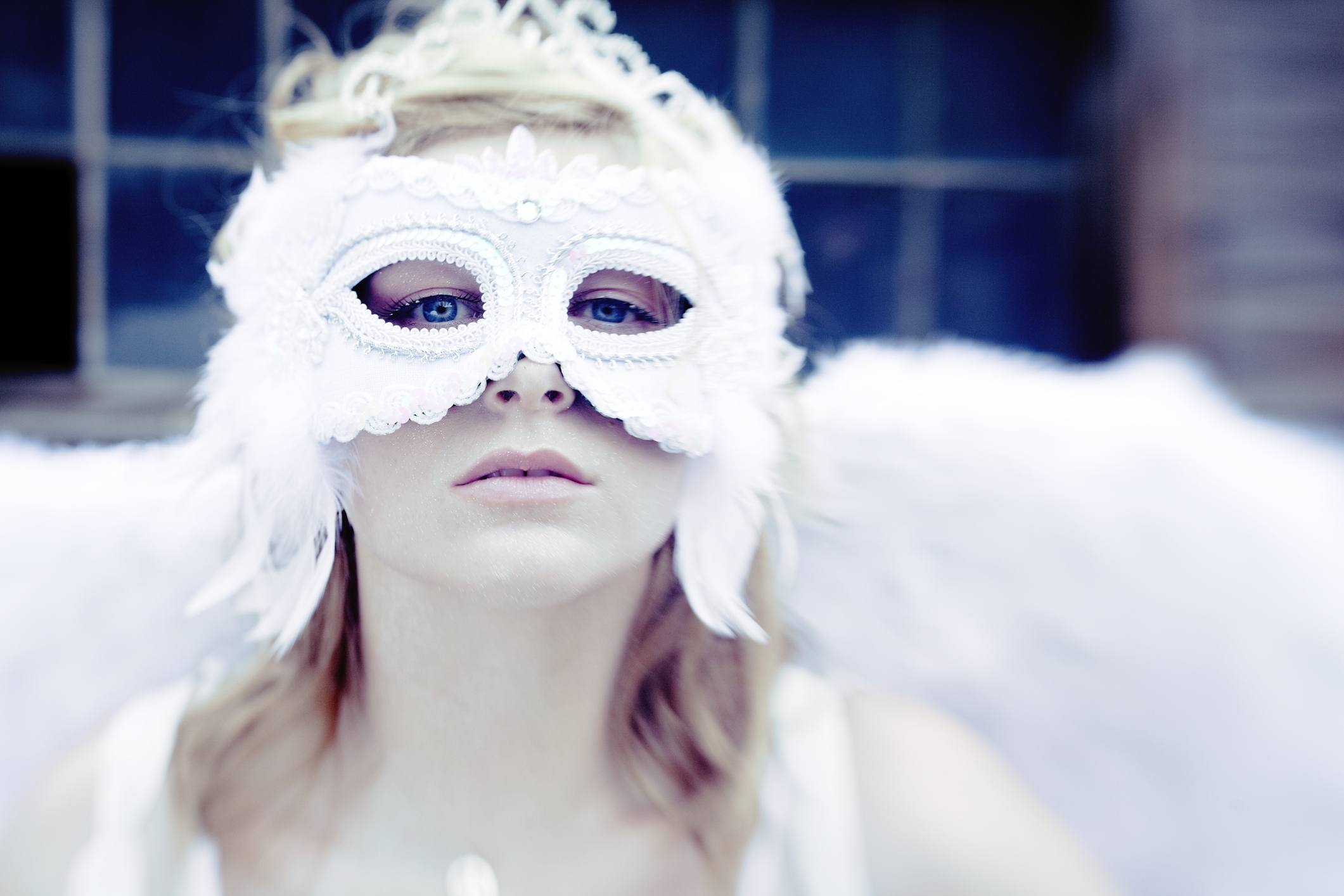 A woman in a mask dressed as an angel.