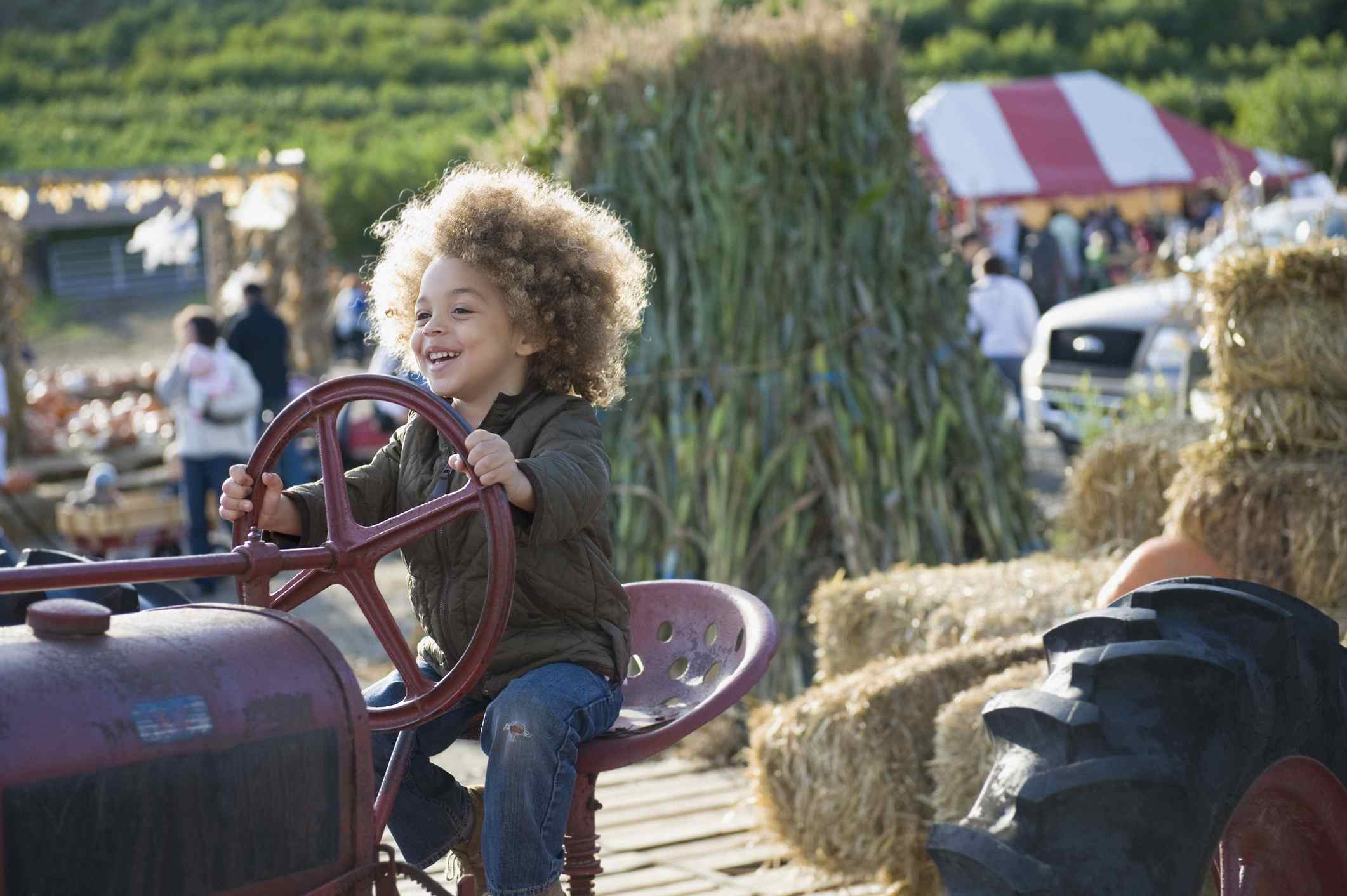 A boy plays on a tractor at a harvest festival