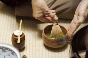 Man stirs matcha with a whisk