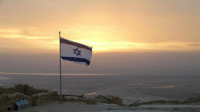 Flag of Israel flying over a sunset landscape.