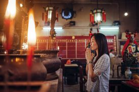 Woman praying in a temple in China