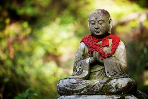 A stone statue of Buddha wearing scarf in Japan