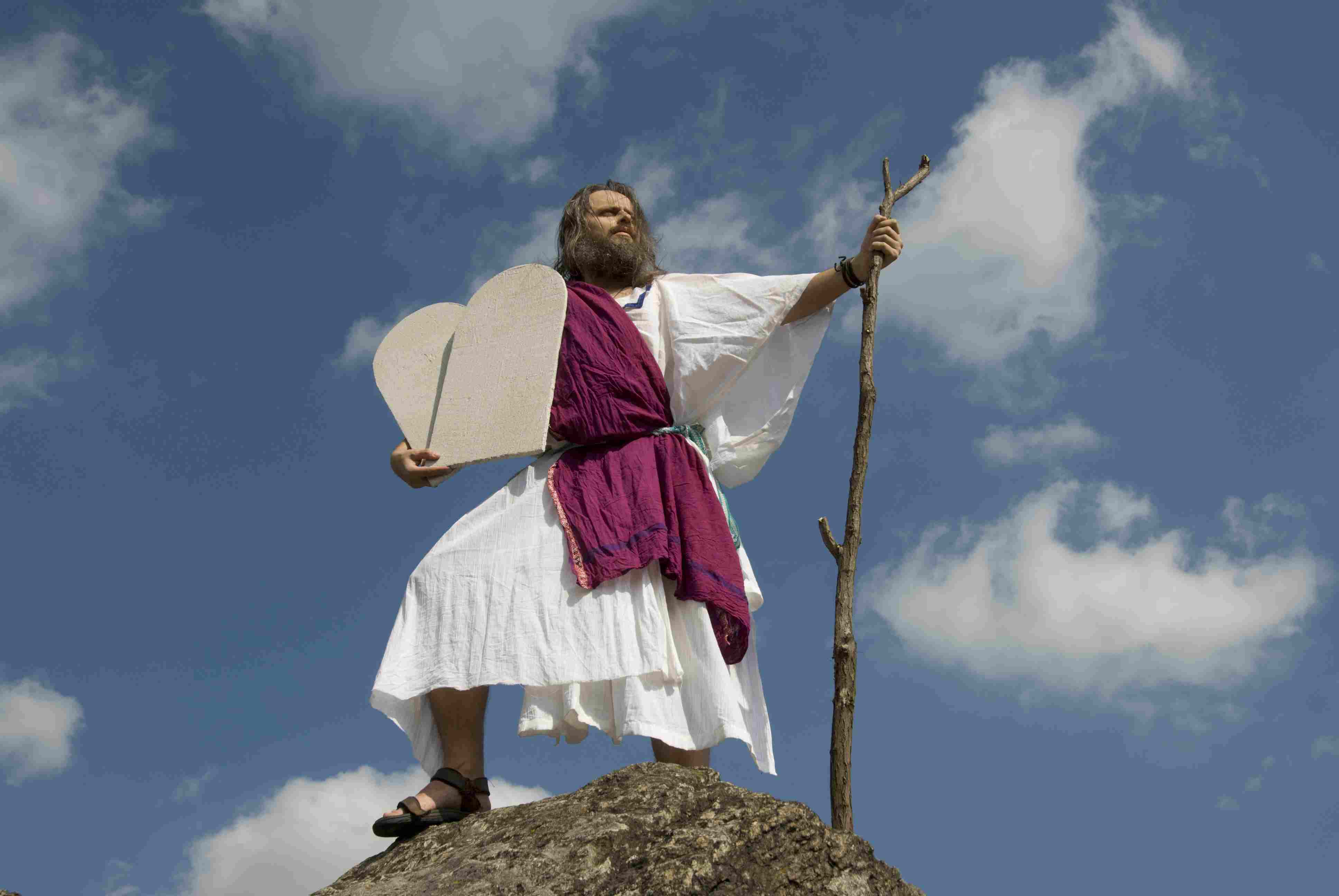 A man dressed as Moses standing on a hill.