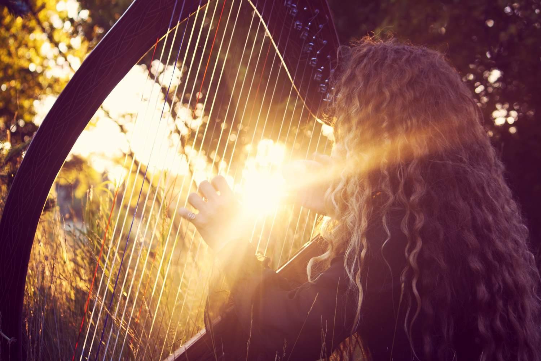Woman Playing Harp in Sunlight