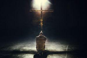 man kneeling at the cross