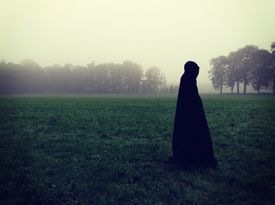 Silhouetted Cloaked Figure