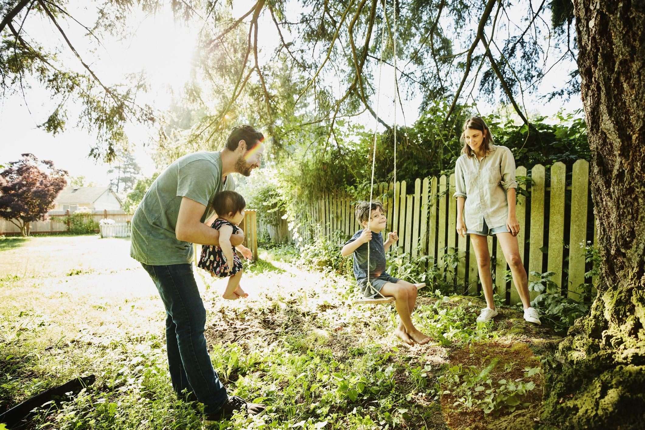 Family using swing in backyard