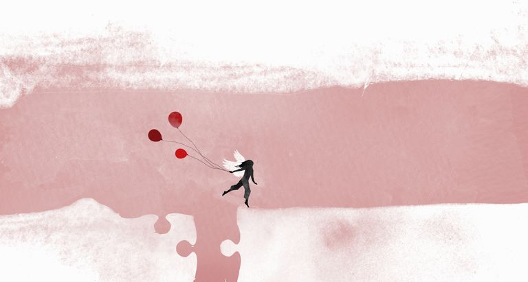 Silhouette of woman with wings running holding balloons