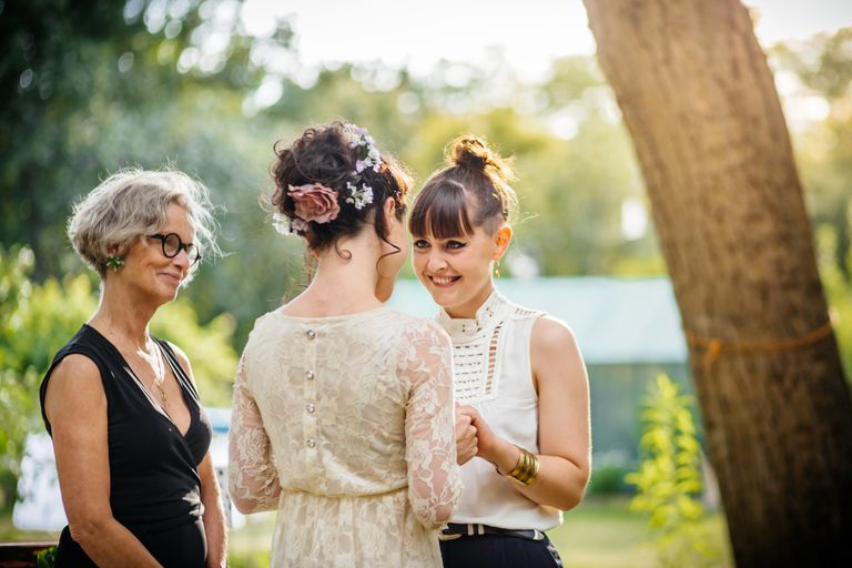 Lesbian couple and registrar standing at the alter