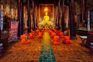Buddhist monks meditate inside the Wat Phan Tao, Chiang Mai