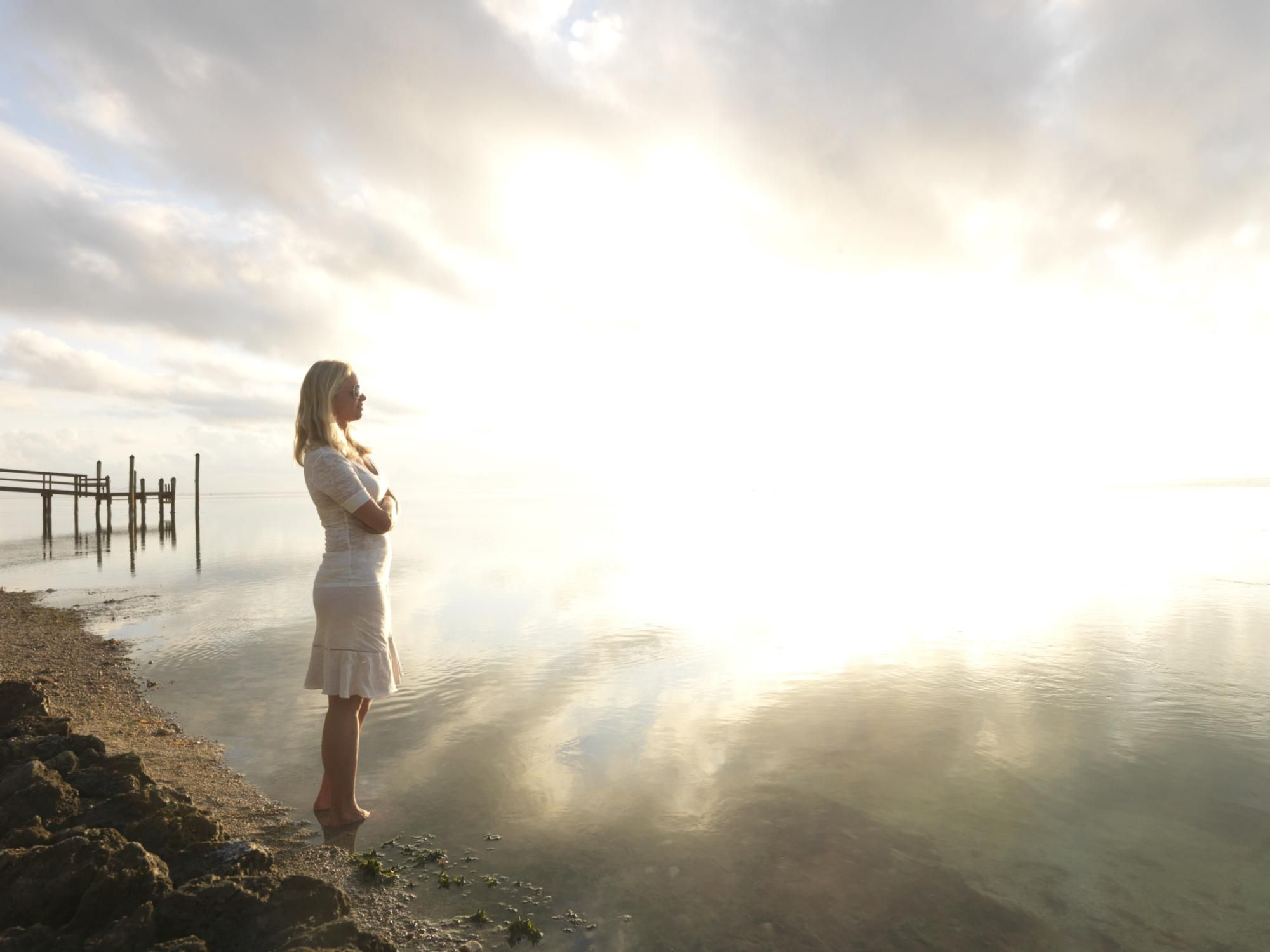 woman in white wading into the ocean with bright light