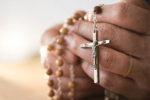 USA, New Jersey, Woman praying with rosary beads in hands