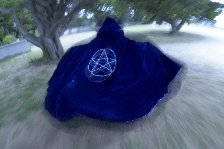 Cloaked figure running away