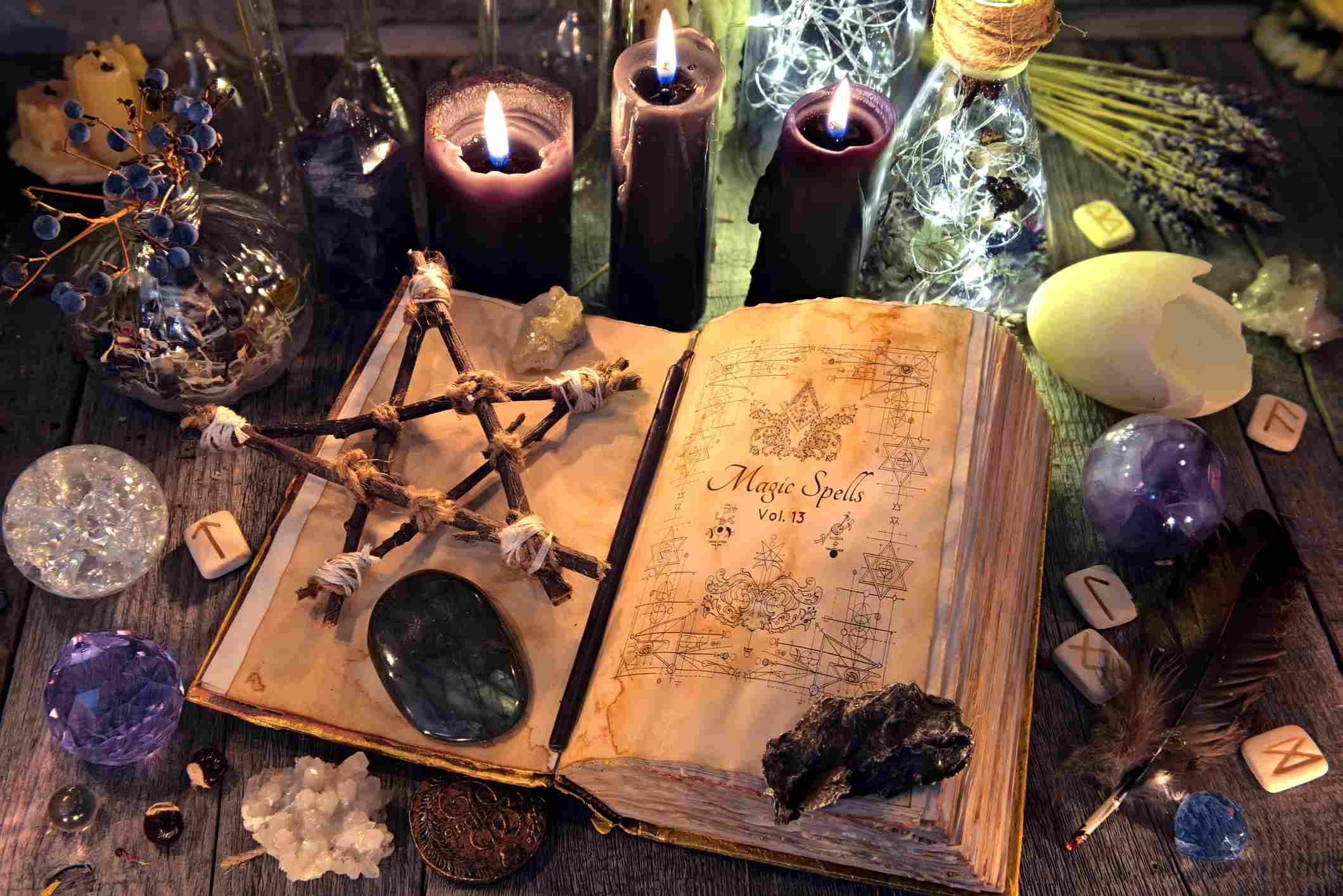 Old witch book with pentagram, black candles, crystals and ritual objects