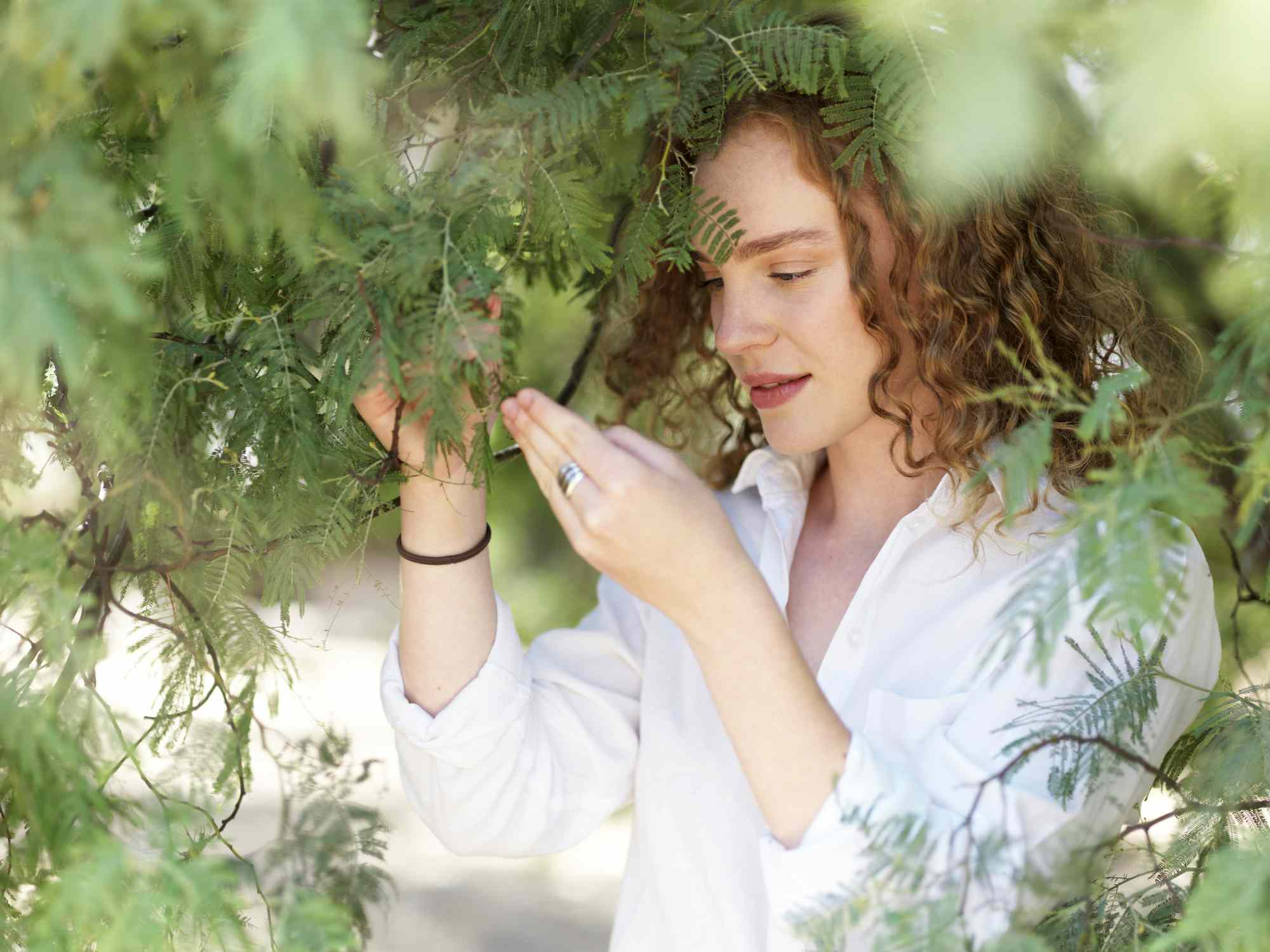 young woman examining the leafes of a tree