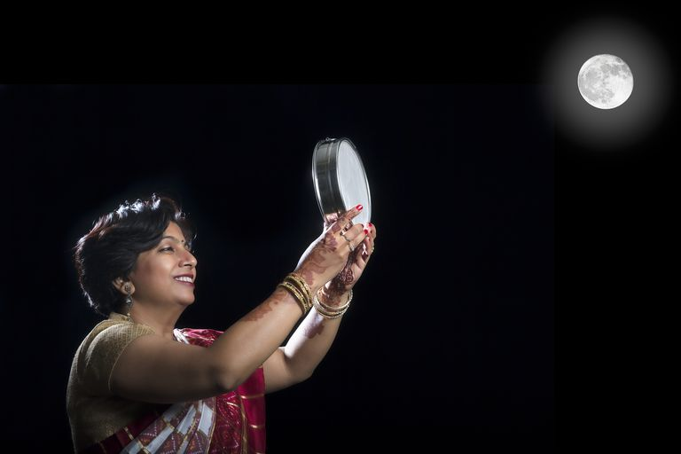 Woman Looking at moon through a sieve during Karva Chauth