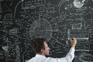 Teacher writing equations on the black board.
