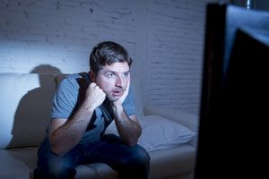 Television addicted man watching tv holding remote control mesmerized
