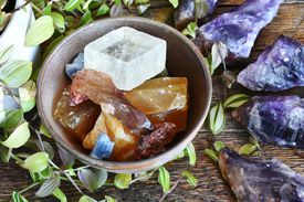 A top view image of a pottery bowl full of various calcite crystals with Canadian amethyst crystals.