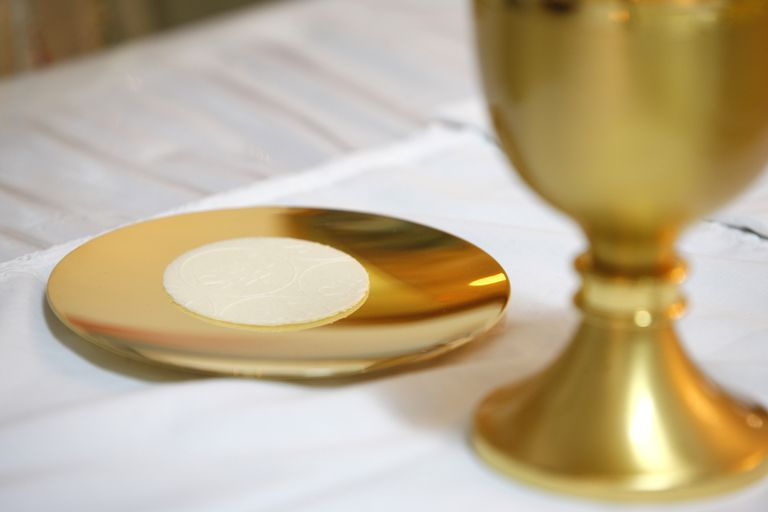 Gold chalice and paten with eucharistic bread for Catholic communion