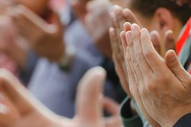 Many hands raised in Muslim prayer or du'a