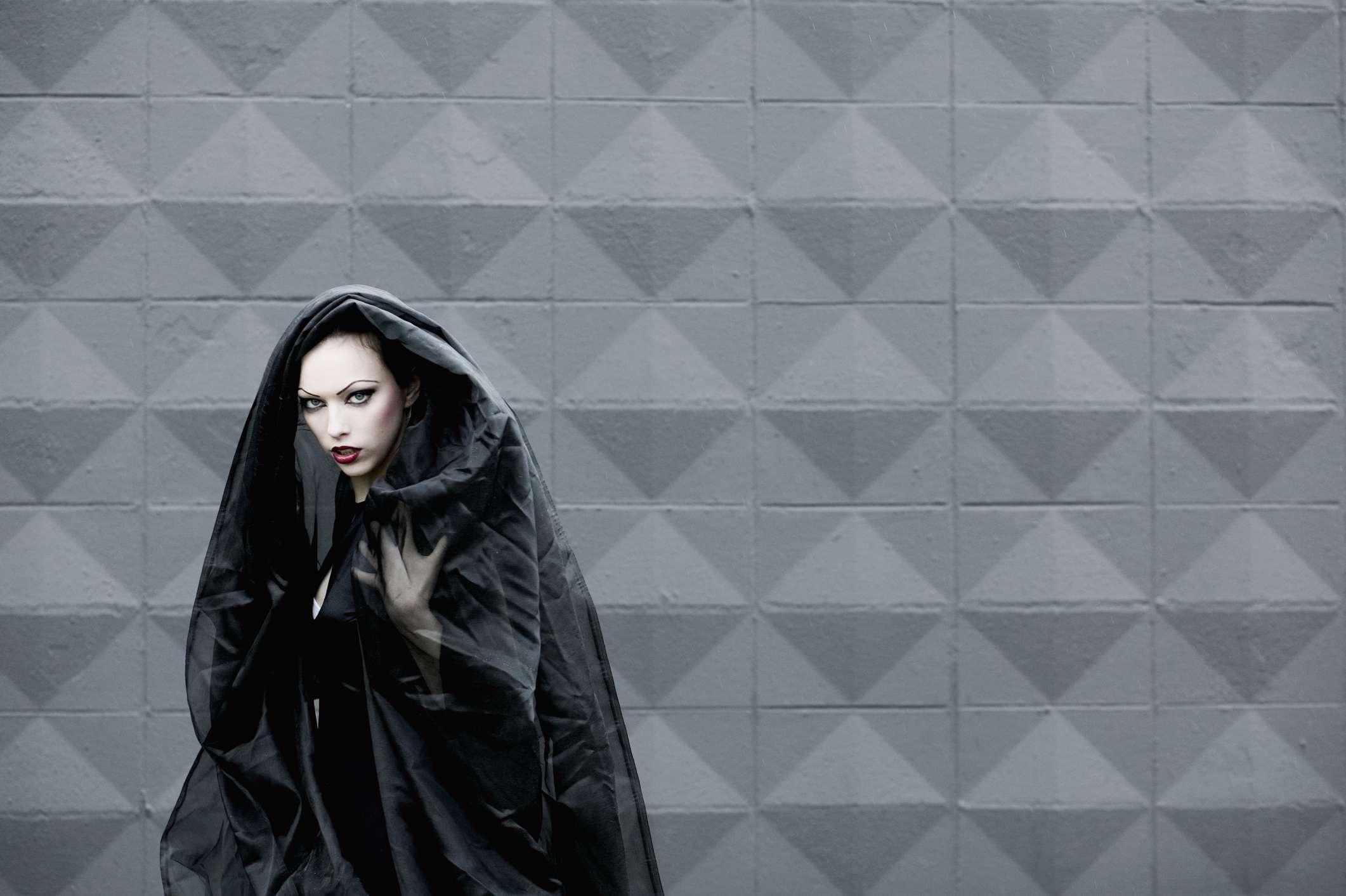 Seductive woman in black cloak