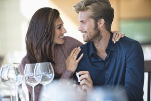 Man with engagement ring proposing to his girlfriend in a restaurant