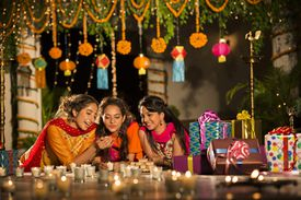Cousins lying on courtyard and holding candle during diwali festival