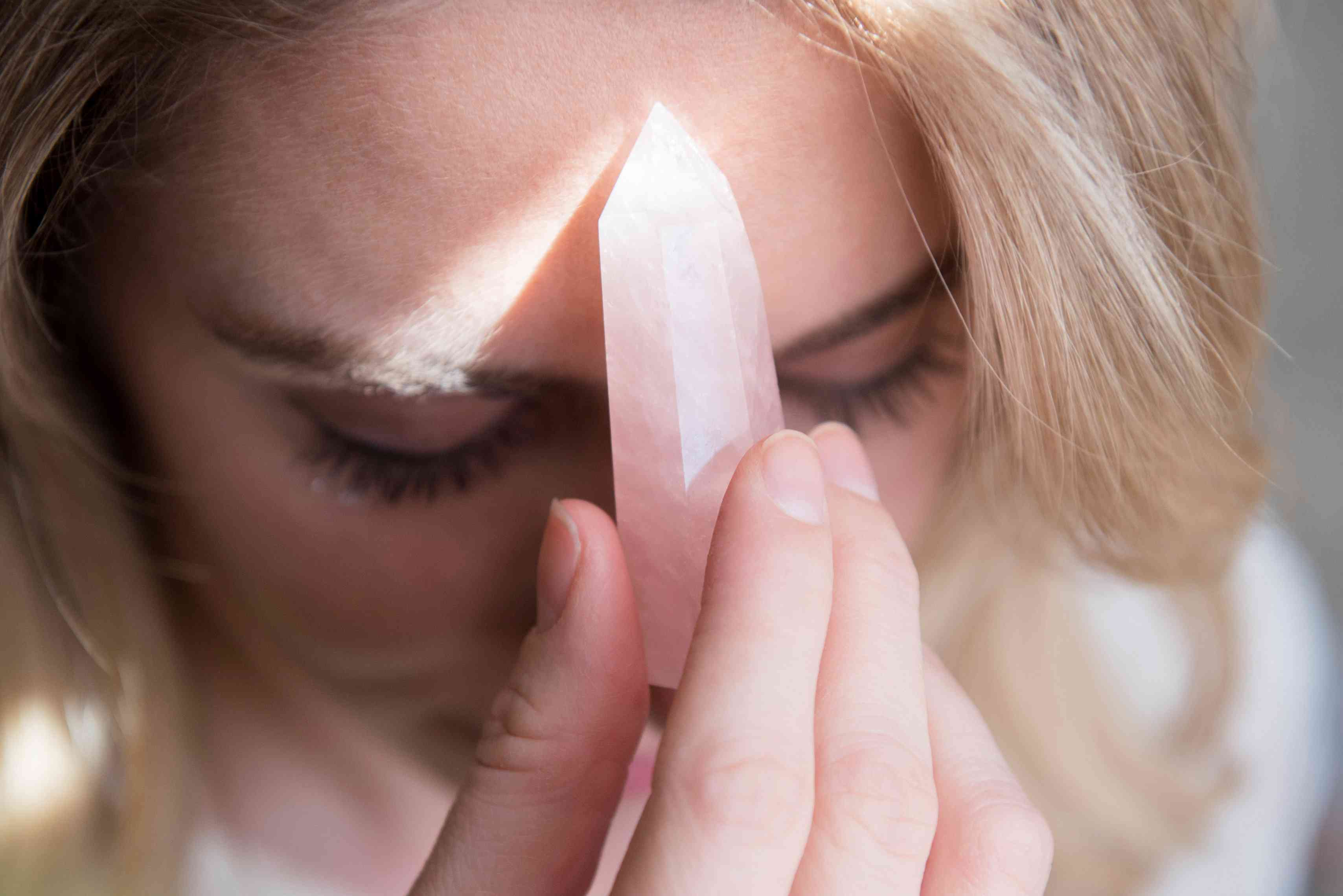 Rose quartz crystal point held to a woman's forehead