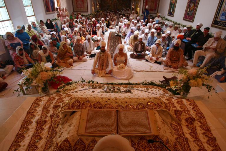 Sikh Bride and Groom Seated Before Guru Granth Sahib in Anand Karaj Wedding Ceremony