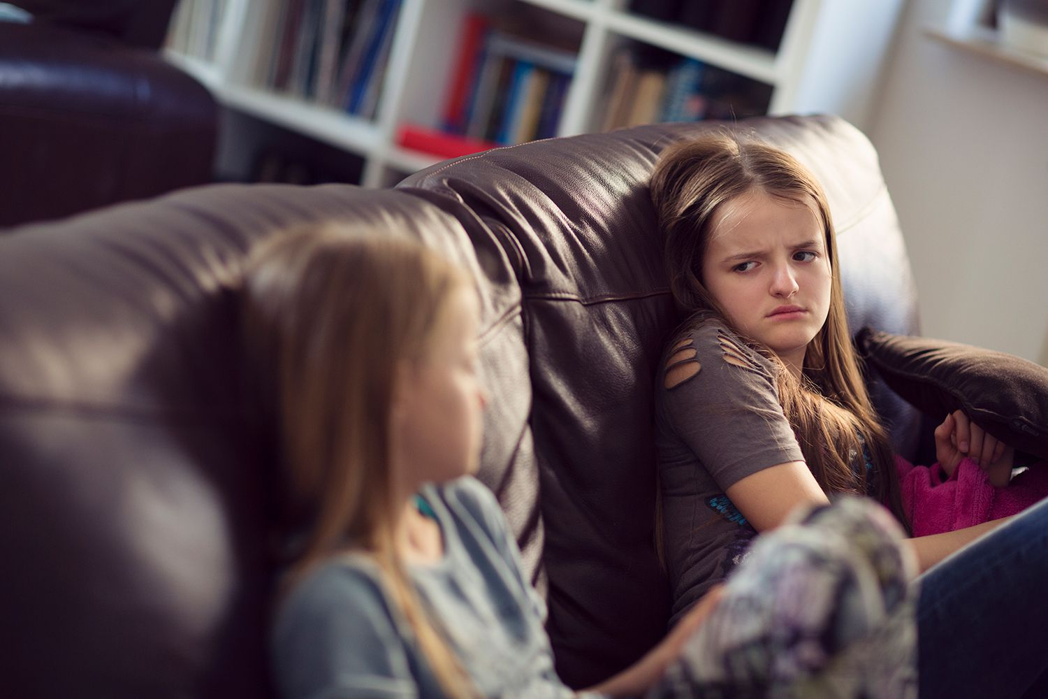 Two adolescent girls sitting on a sofa, annoyed at each other