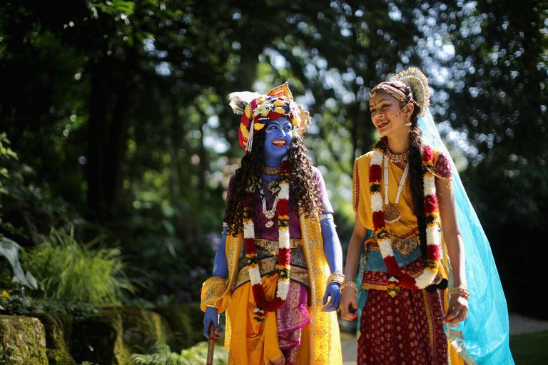 Laxmipriya Patel dressed as the Hindu god Lord Krishna, and her sister Mohini Patel dressed as Lord Krishna's devotee Radharani, walk through the George Harrison Memorial Garden during the Janmashtami Hindu Festival