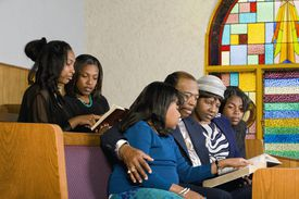 African Americans looking at bibles in church