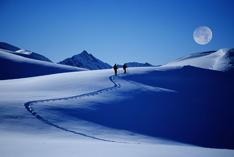 Young couple snowshoeing in mountains