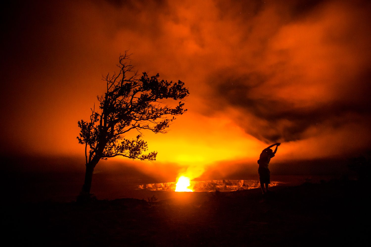A person is silhouetted against the fires of a volcano