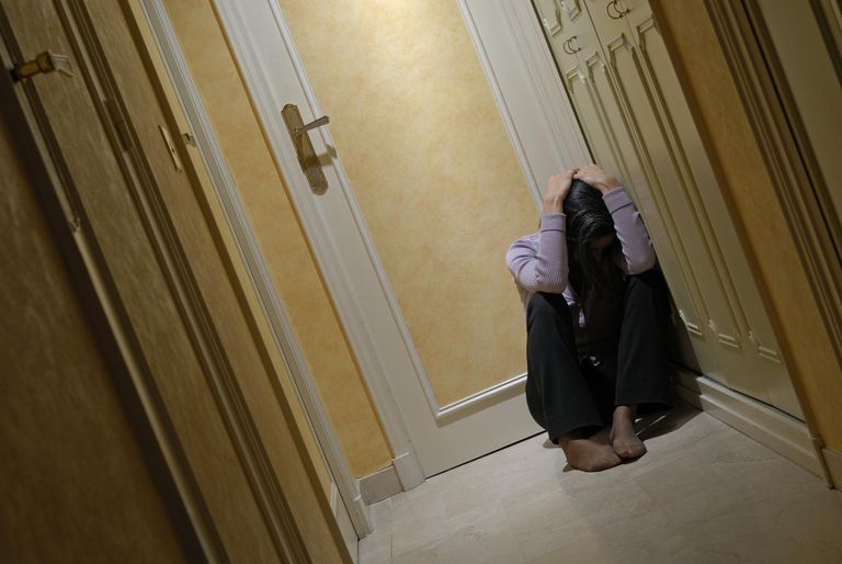 Woman sitting in corridor with head in hands