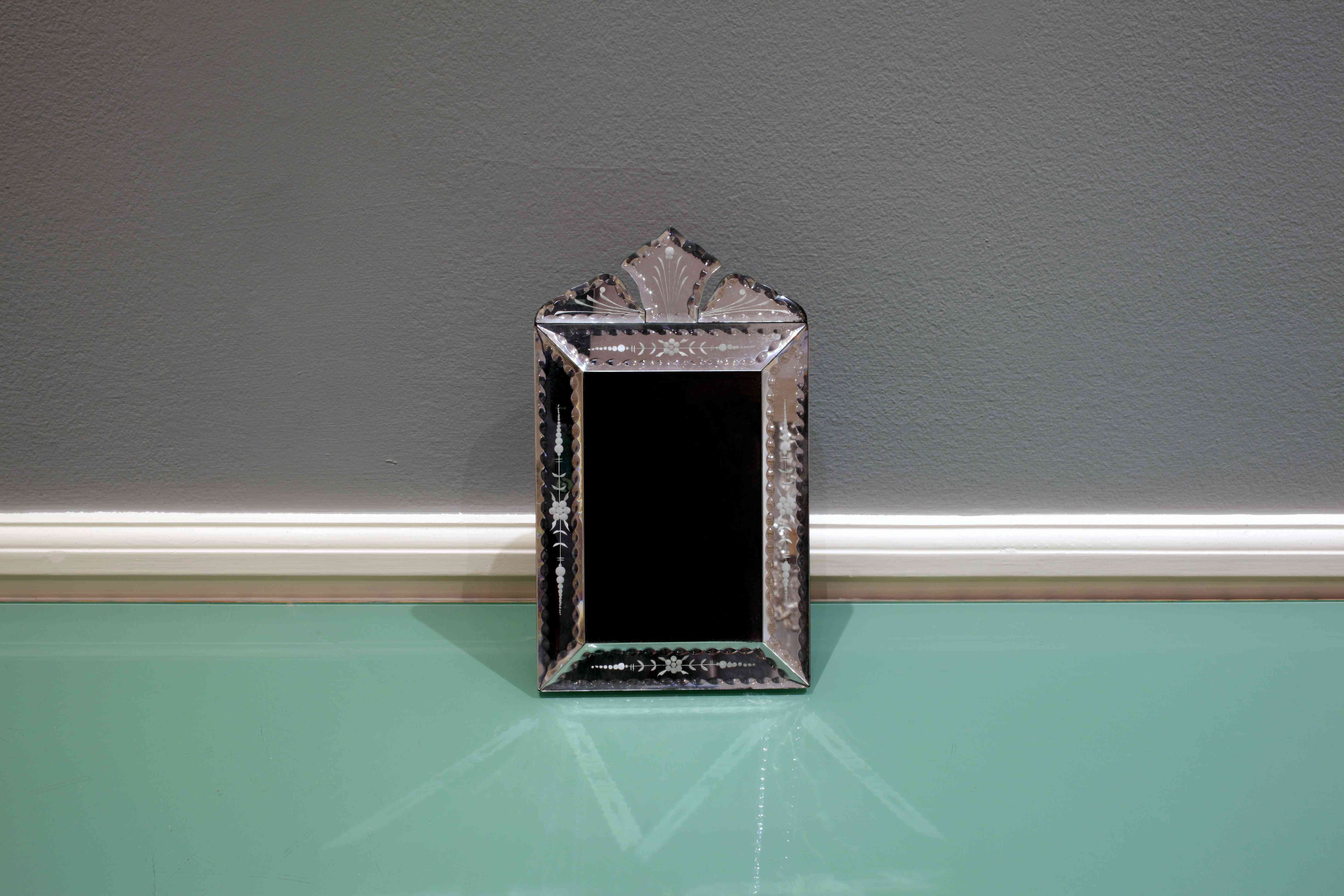 Handcrafted Venetian mirror on a green glass table inside a room