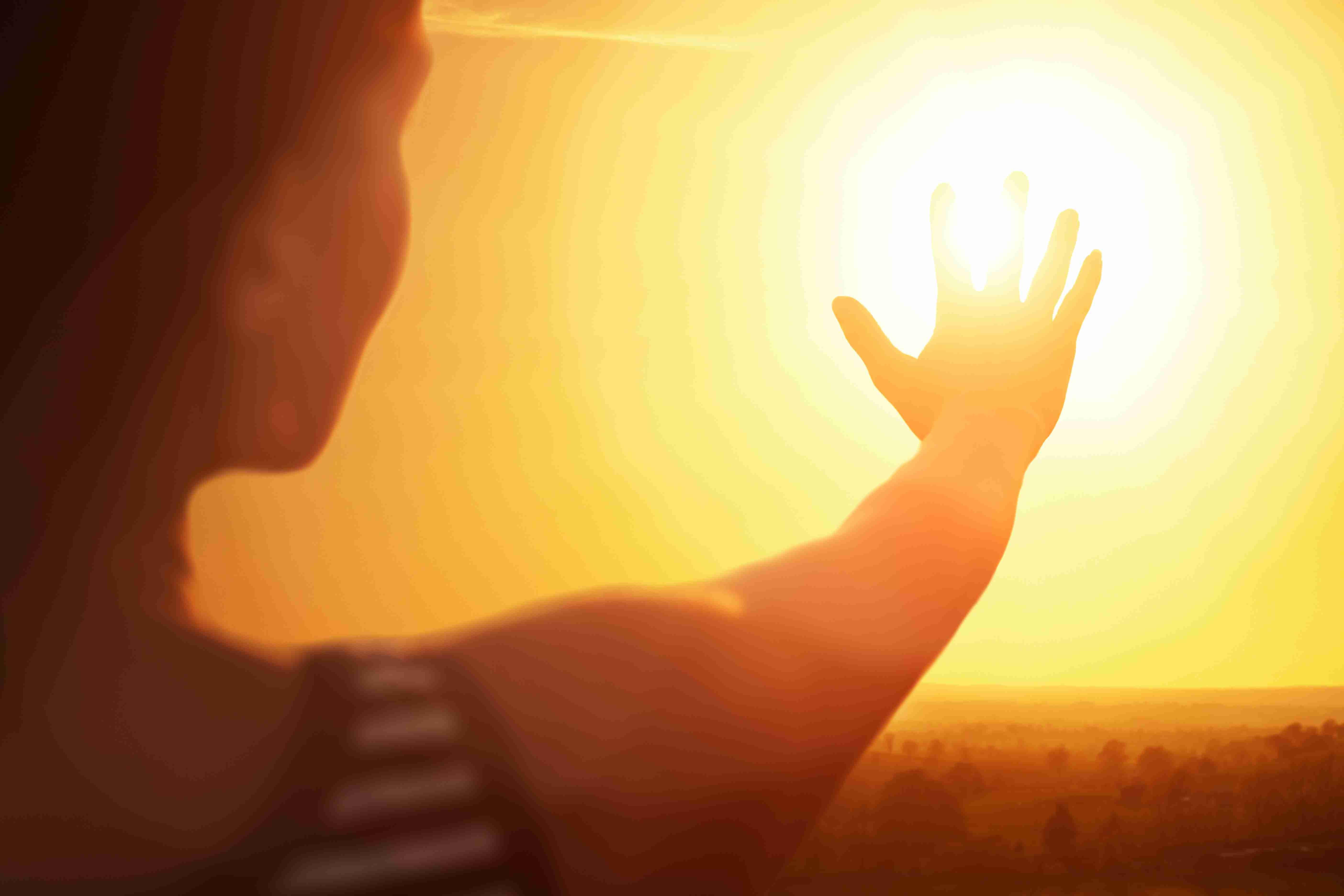 Woman reaching for the sun.