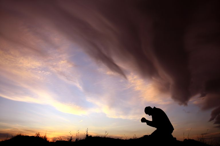 Silhouette of Man Praying During Storm