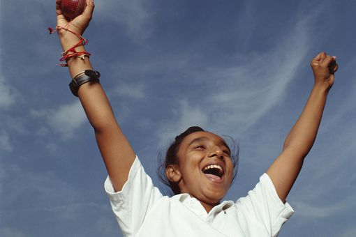 Boy (10-12) holding cricket ball with arms raised, shouting