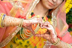 heart hape of Hands of an Indian bride painted with henna