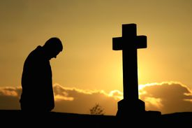 Person kneeling before a cross