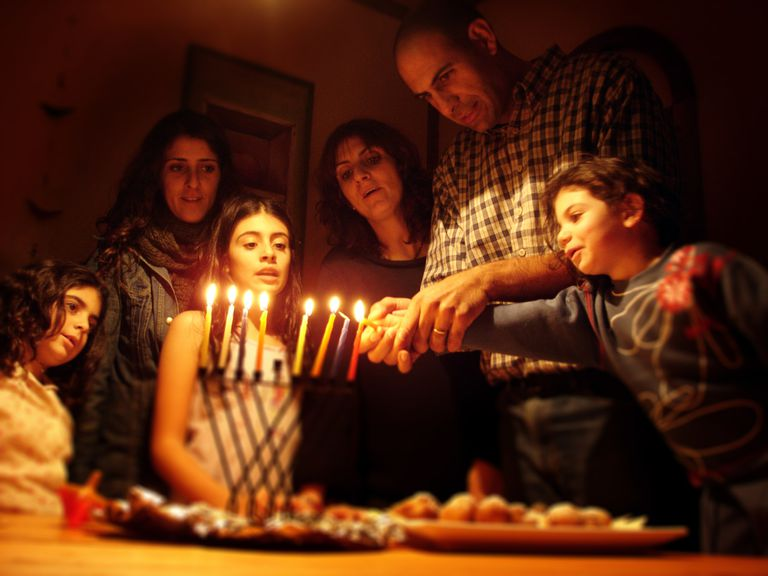 Family gathered around a menorah; the father and youngest child are lighting the seventh candle.