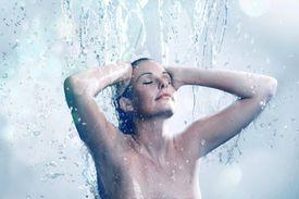 Beautiful woman bathing under running water