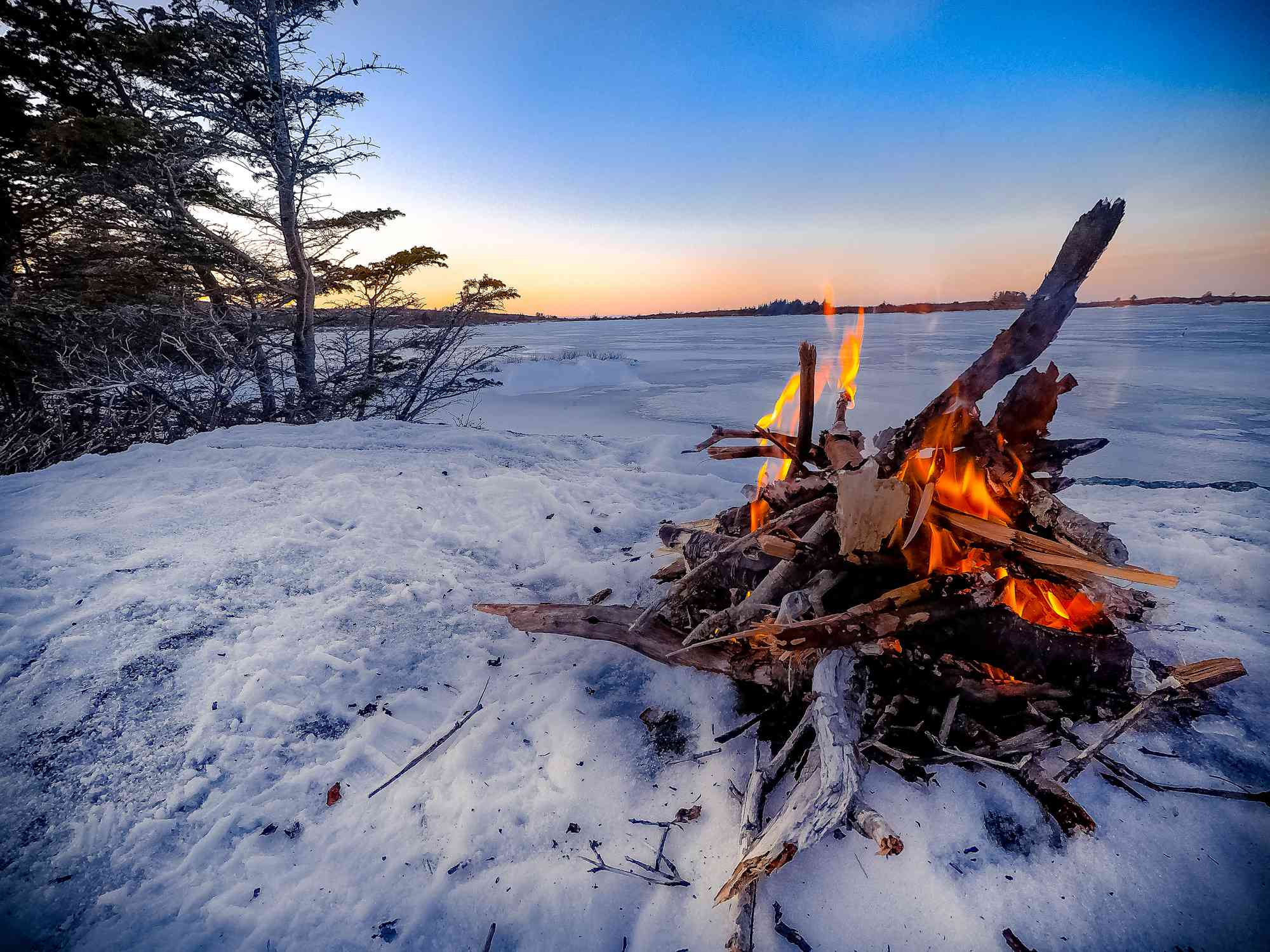 Fire On Snow Covered Field Against Sky During Sunset