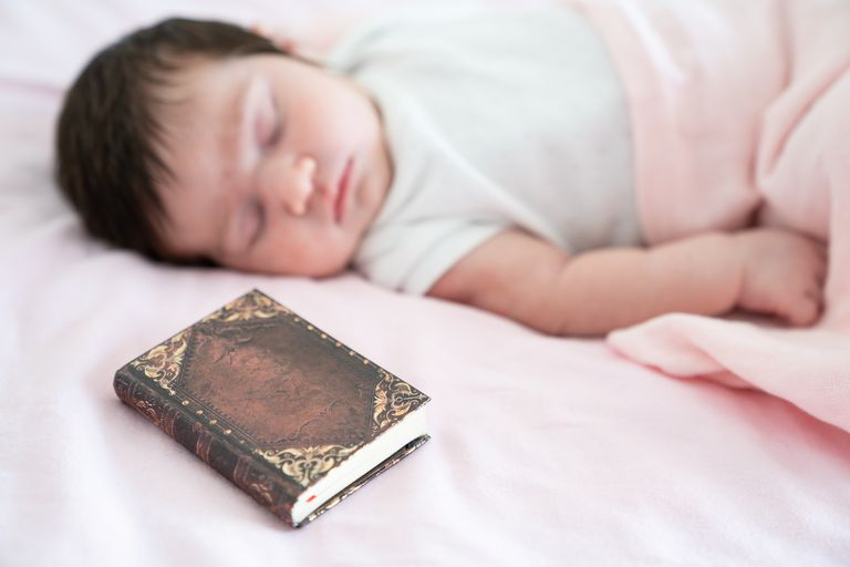 Newborn baby girl sleeping on bed with Bible