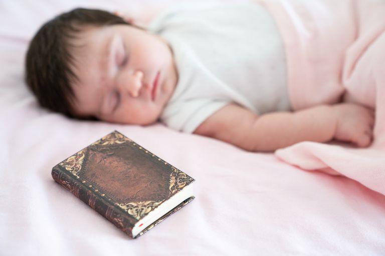 Newborn baby girl sleeping on bed with Bible